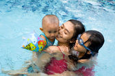 Asian mother and children swim together — Stock Photo
