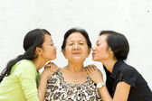 Two granddaughter kiss their old grandmother — Stock Photo
