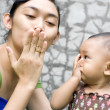 Ethic mother teach baby girl a goodbye kiss — Stock Photo