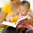 Ethnic young mother reading while babysitting child — Stock Photo