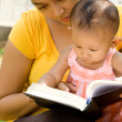 Ethnic mother and baby read a book — Stock Photo