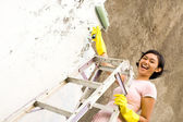 Happy asian girl painting house — ストック写真