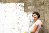 Happy ethnic yougn woman painting house — Stock Photo
