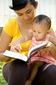 Ethnic young mother reading while babysitting child — Stock Photo