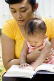 Ethnic mother read a book with child — Stock Photo