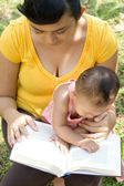 Ethnic mother reading while babysit — Stock Photo