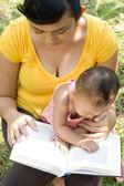 Ethnic mother reading while babysit — Stock Photo
