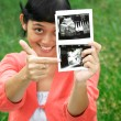 Asian pregnant woman pointing ultrasound scan result - Stock Photo