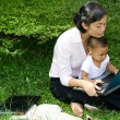 Working mother and child in front of laptop computer — Stock Photo