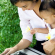 Stock Photo: Working mom babysit baby with laptop