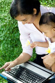 Working mom babysit baby with laptop — Stock Photo