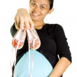 Pregnant woman holding pair of baby shoes - Stock Photo