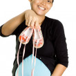 Pregnant ethnic young woman happy showing baby shoes - Stock Photo