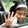 Child waving goodbye from inside a car - Stock Photo