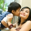 Asian boy kissing mother — Stock Photo