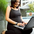 Asian pregnant woman happy working with laptop — Stock Photo