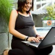 Asipregnant womhappy working with laptop — Stock Photo #9380372
