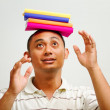 Ethnic young man balancing books on head — Stock Photo #9513528