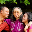 Happy asian young man and woman embrace old mother — Stock Photo