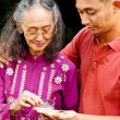 Ethnic young man help elderly woman taking medicine — Stock Photo #9711554