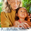 Ethnic child and grandmother playing piano — Stock Photo