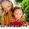 Ethnic child and grandmother playing piano — Stock Photo #9713350
