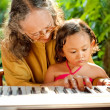 Stock Photo: Asian senior woman and child playing piano