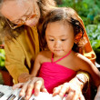 Ethnic elderly woman teach child play piano — Stock Photo