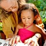 Ethnic elderly woman teach child play piano — Stock Photo