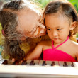 Ethnic child and grandma playing piano together — Stock Photo