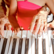 Hands of old woman and child playing piano — Stockfoto