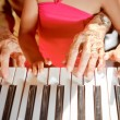 Hands of old woman and child playing piano — Stock Photo