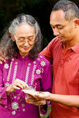 Ethnic young man help elderly woman taking medicine — Stock Photo