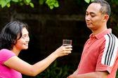 Mujer joven étnica ofreciendo agua mineral pura a amigo — Foto de Stock