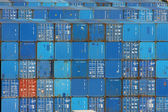 Stack of blue sea containers in an international port container shipping — Stock Photo