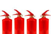 Four fire extinguishers — Stock Photo