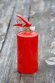 Extinguisher on the wooden sidewalk — Stock Photo