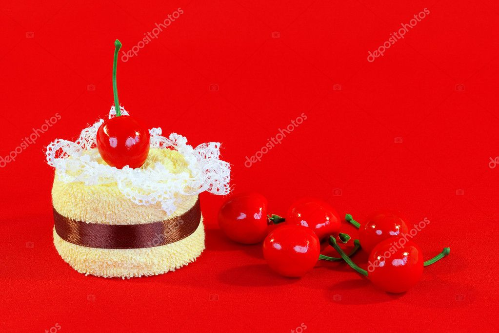 Rolled up towel with toy cherries on red background — Stock Photo #9214109
