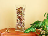Glass vase filled with flower petals — Stock Photo