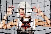 Moda ragazza dietro una mesh — Foto Stock