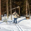Young man cross-country skiing through the forest — Stock Photo