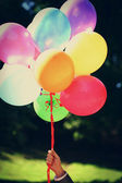 Wakacje powietrza kolorowe balony w rękę — Zdjęcie stockowe