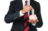 Businessman Putting Money in Piggy Bank — Stock Photo