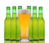 Vaso de cerveza con botellas detrás — Foto de Stock