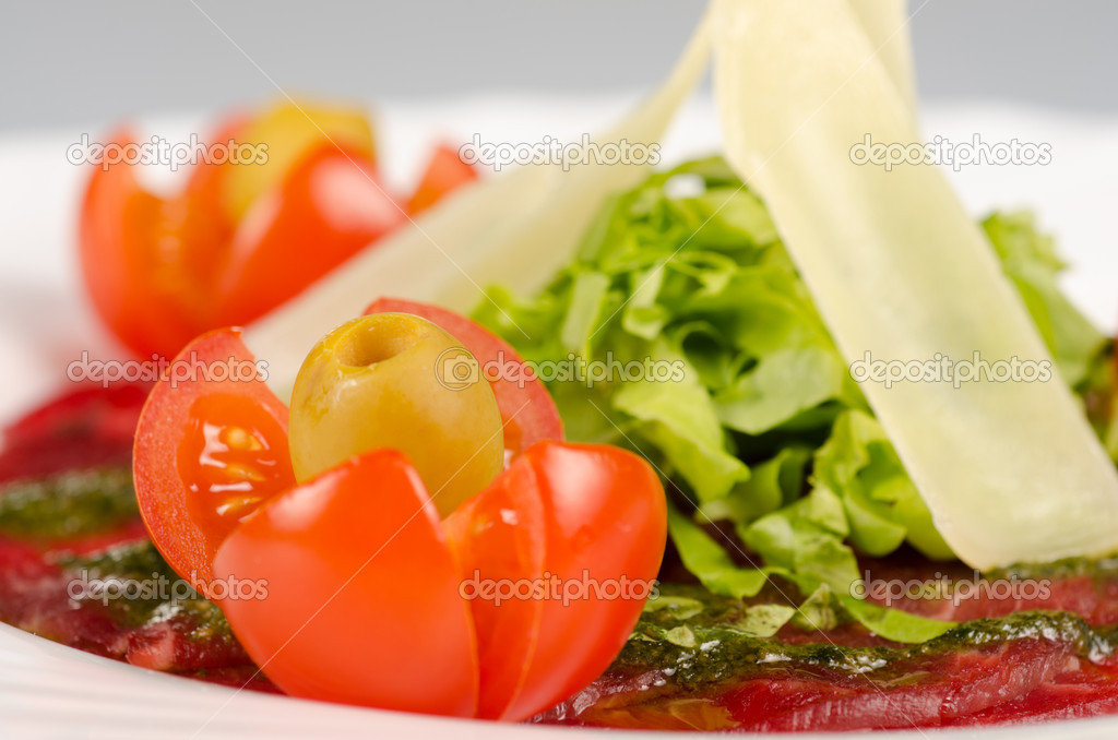 Meat carpaccio from beef meat, parmesan cheese, olive, tomato, sauce pesto — Stock Photo #9983541