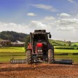 Tractor working the land - Stock Photo