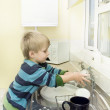 Little boy in the kitchen washing taps. — Stock Photo #9801087