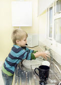 Little boy in the kitchen washing taps. — Stock Photo