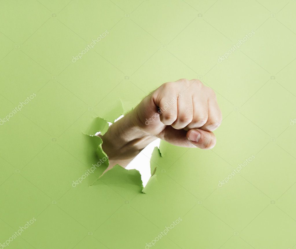 Man punching through green cardboard with his fist. — Stock Photo #10391588