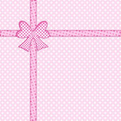 Bow and ribbon on pink polka dot background — Stock Photo